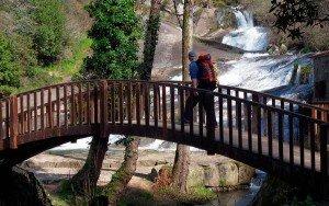 Puente de madera atravesando un río caudaloso.